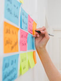 photo of person writing on sticky notes